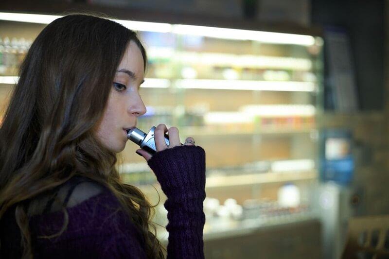 Moça dentro um estabelecimento utilizando o seu cigarro eletrônico de forma discreta para evitar acidentes