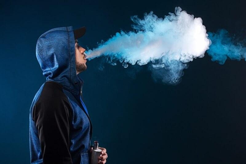 Jovem de jaqueta azul exalando nuvem após uso contínuo do vape