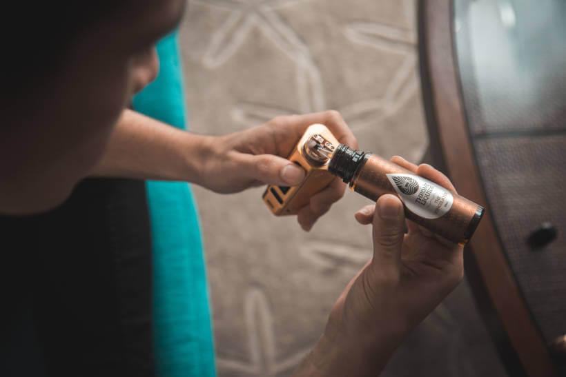 Jovem reabastecendo cigarro eletrônico, evidenciando uma das desvantagens do uso de vape