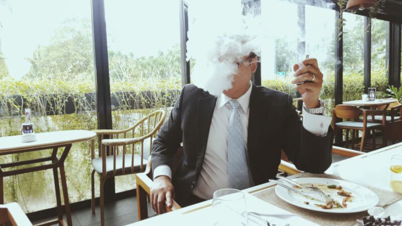 Senhor em restaurante após saber dos efeitos colaterais do vape que está utilizando