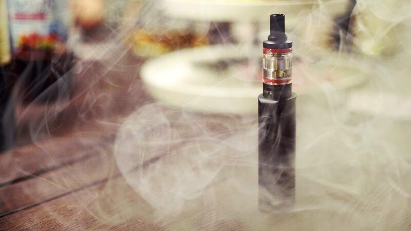Vape sobre a mesa com uma leve nuvem de juice de tabaco pela imagem