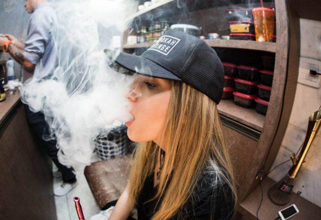 Mulher de bone preto após comprar nicotina para vape