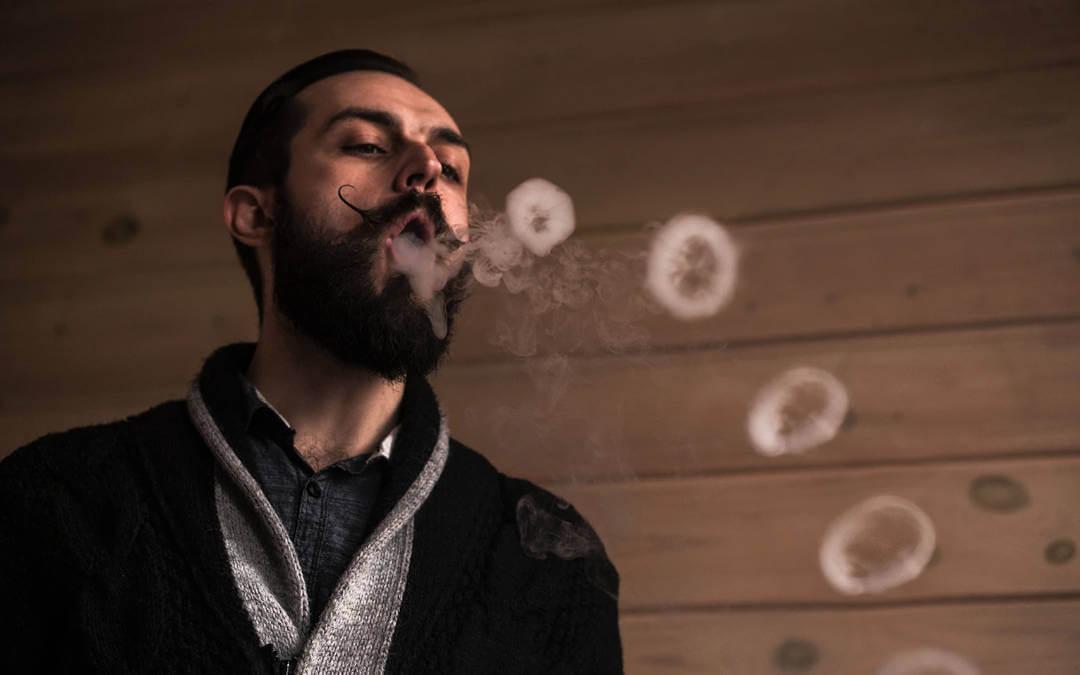 Homem de barba fazendo anéis de fumaça